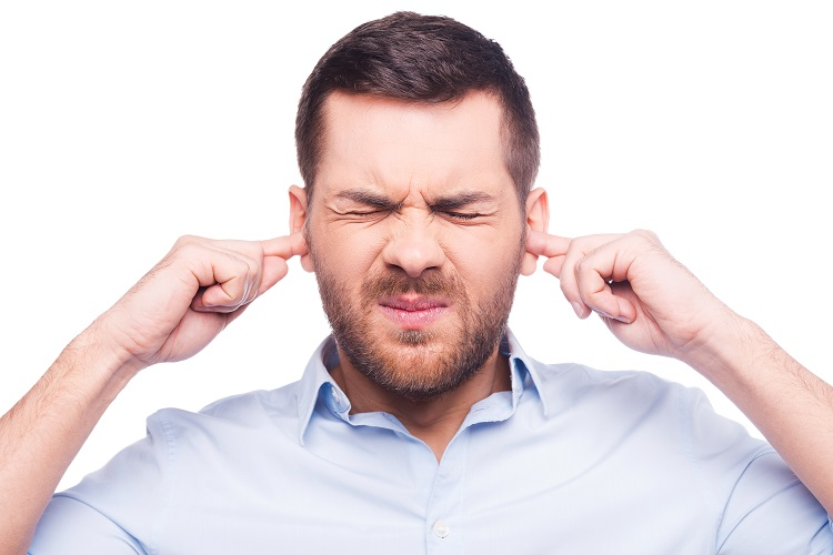 This is too loud! Frustrated mature man in shirt holding fingers in his ears and keeping eyes closed while standing against white background